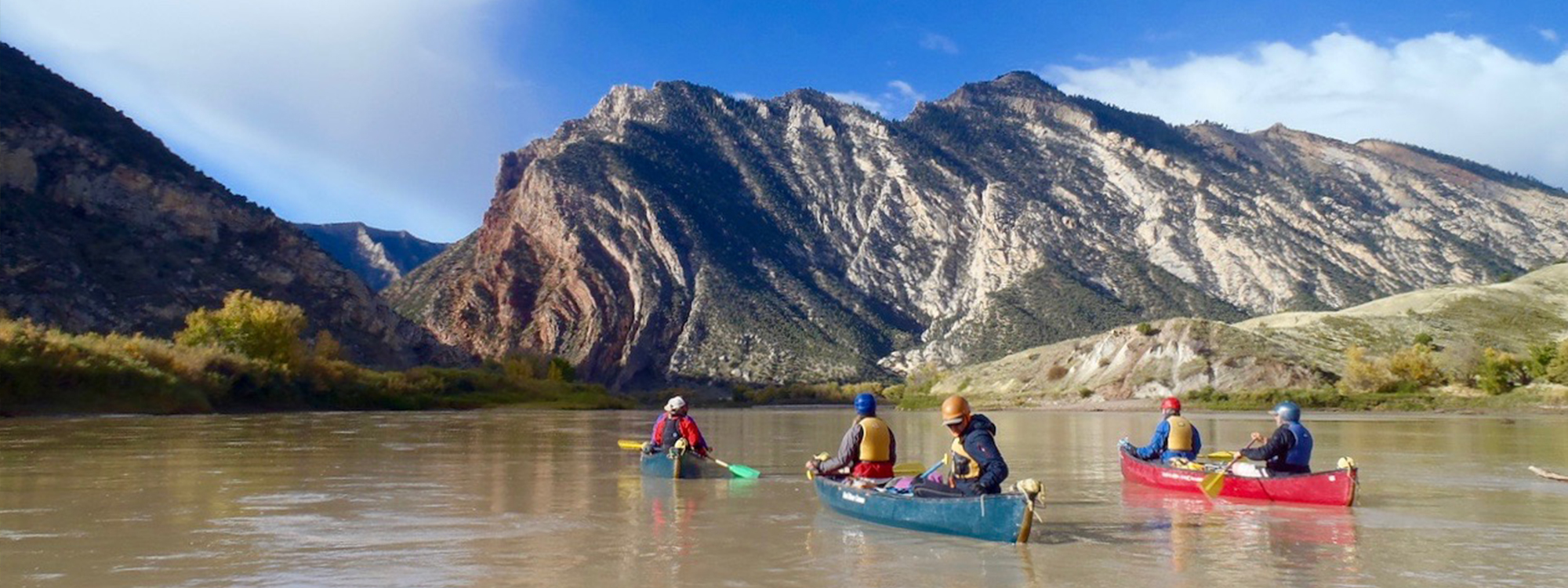 People kayaking with mountains in the background