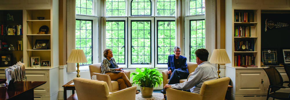 President John D. Simon in discussion with colleagues
