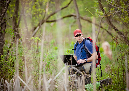 A Lehigh student holding a laptop in a forest