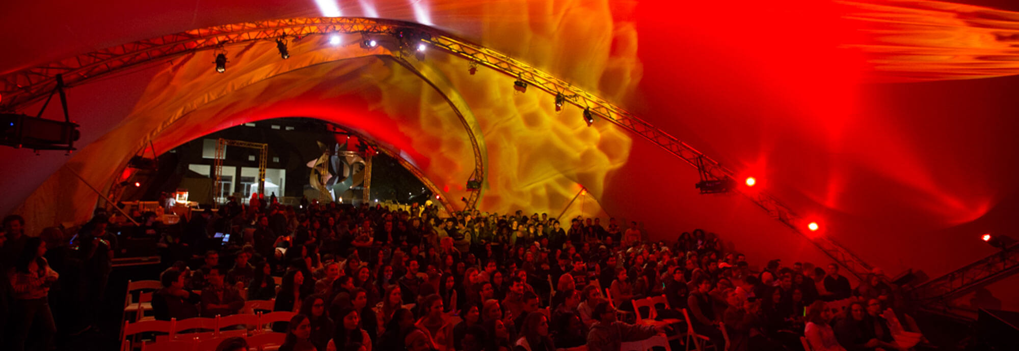 Attendees under a tent at night