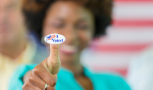Image of I Voted sticker on woman's thumb, blurry woman in background.