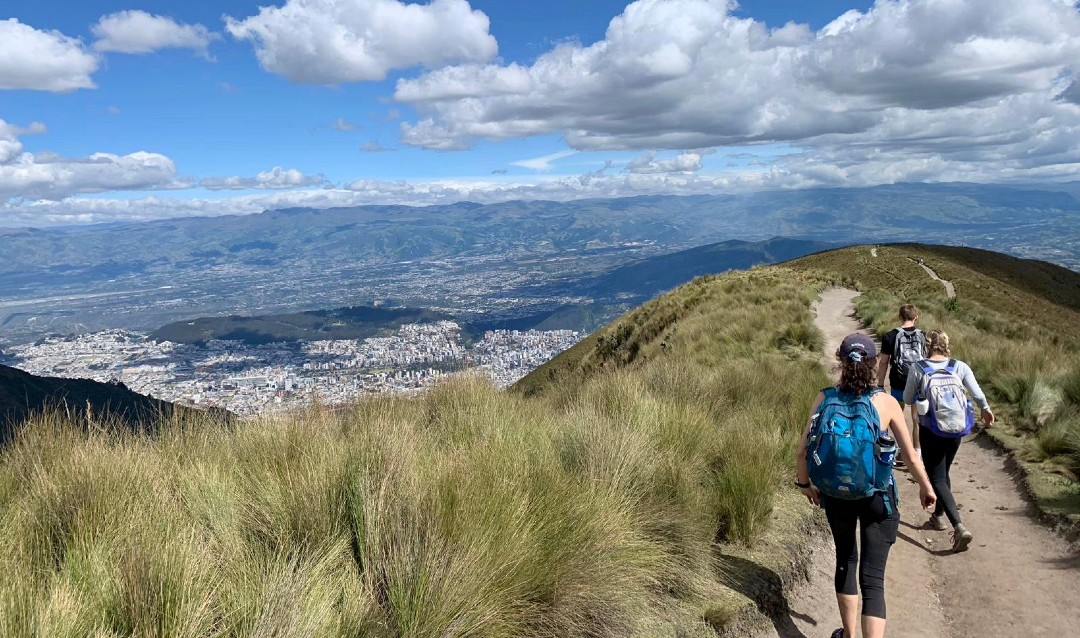 Students hiking on mountain near Quito, Ecuador with a view of the city below.
